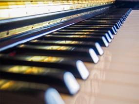 金色に輝くアップライトピアノの鍵盤
