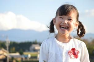 田舎の町と雪山を背景に笑う女の子