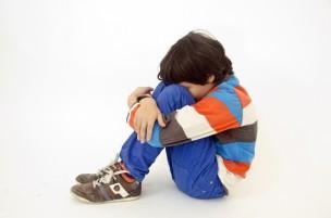 膝を抱えていじける男の子の写真
