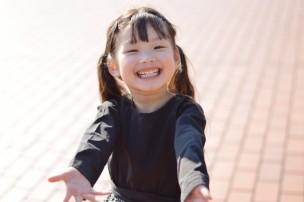 腕を広げて笑う幼児の女の子