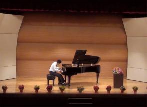発表会でピアノを弾く高校生の男の子