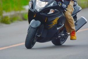 黒いカッコイイバイクが道路を走る様子