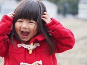 赤いコートを着た女の子が笑っている写真
