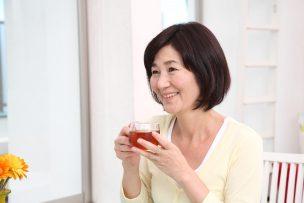 紅茶を飲みながら笑顔で話す女性