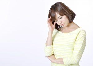 頭を抱えて思案するショートヘアの女性