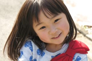 上を向いて微笑む幼児の女の子
