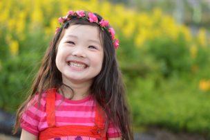 お花畑をバックに花輪を被る笑顔の女の子