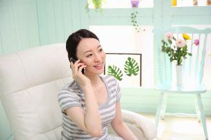 電話をかける大人の女性の写真