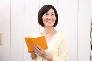 手帳を見て笑う大人の女性