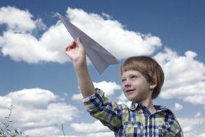 青空の下紙飛行機を飛ばす男の子