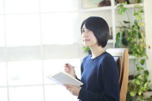 本とペンを持って勉強する女性